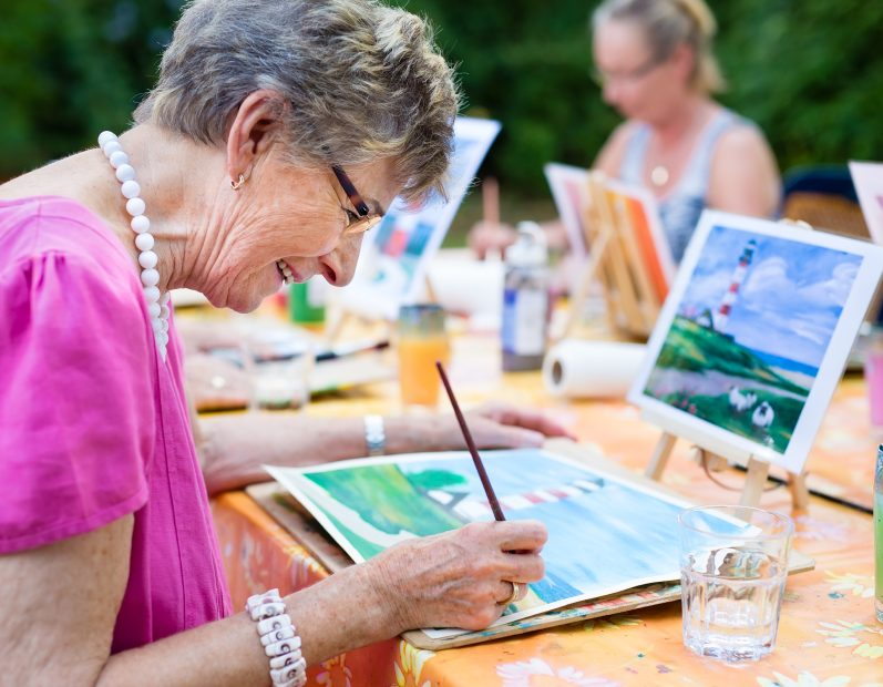 Senior woman painting with water colors