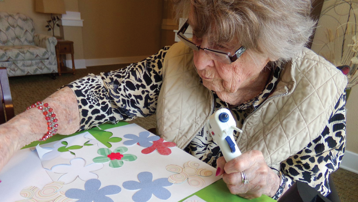 Female resident creating a collage and using a glue gun.
