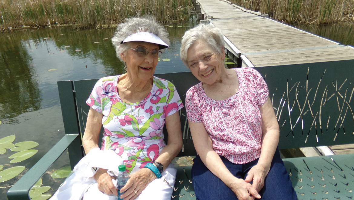 Two female resident's sitting on the dock chatting