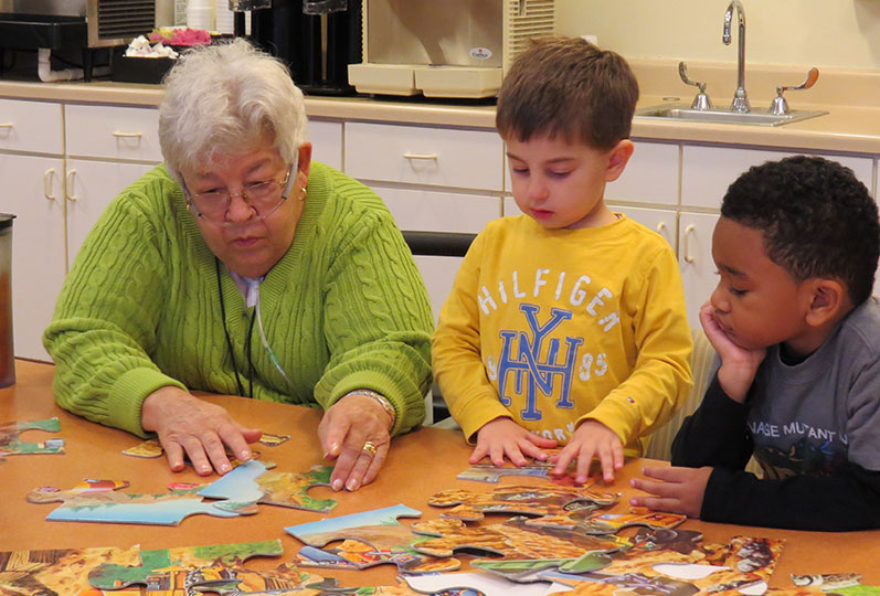 Senior resident putting a puzzle together with two children